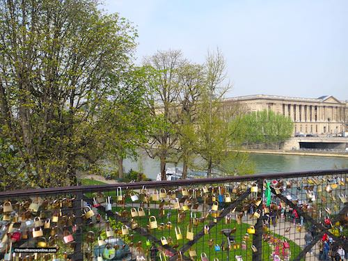 Love locks on Pont-Neuf with Louvre in the background