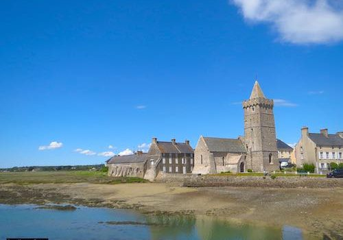 Fortified Notre-Dame de Portbail Church by the harbour and sea at low tide